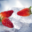 Three strawberries on ice — Stock Photo