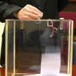 Stock Photo: Ballot box and hand putting a ballot in