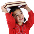 Little girl thinking while holding books - Stock Photo