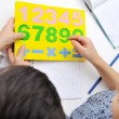 Little boy counting, numbers on table - Stock Photo