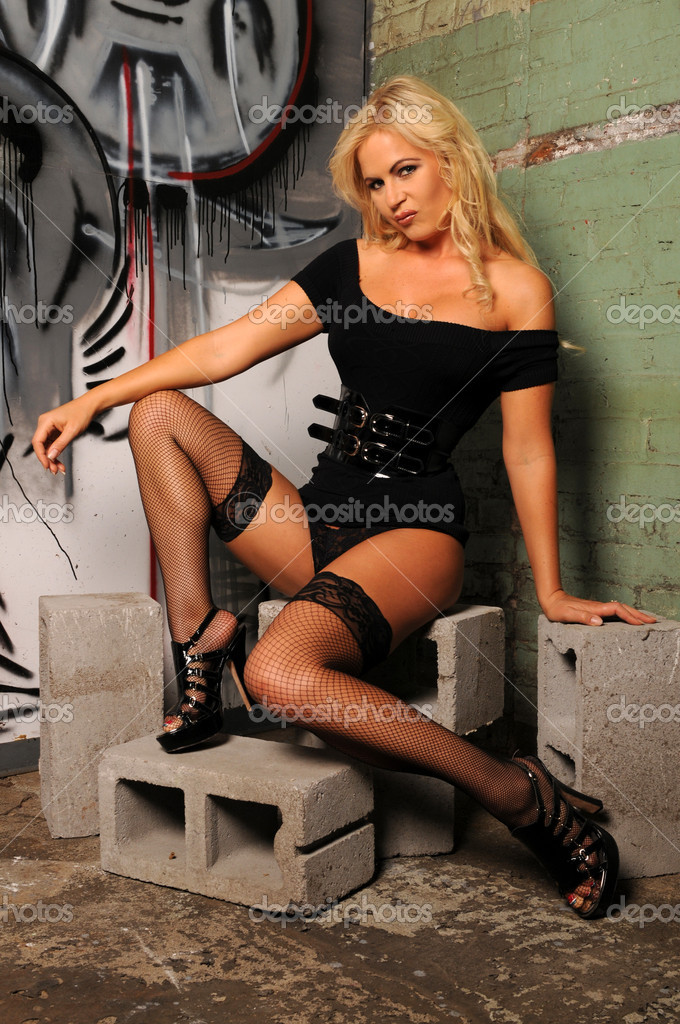 Beautiful blonde in black lingerie sitting on cinderblocks  Stock Photo #4014190