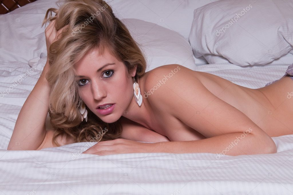 Beautiful young blonde lying nude in bed — Stock Photo #4252679