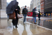 Busy london commuters in the pouring rai — Stock Photo