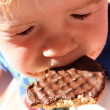 Child eating chocolate biscuit — Stock Photo