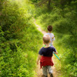 Young children walking in forest — Stok fotoğraf