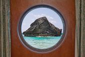 Rock in Ocean through Porthole — Stock Photo