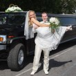 Wedding couple near limousine — Stock Photo