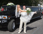 Wedding couple near limousine — Foto Stock