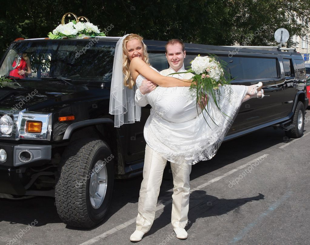 Groom holds  bride on hands near a long wedding  limousine  Stock Photo #2880072