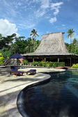 Swimming pool and hut-bar in tropical hotel — Stock Photo