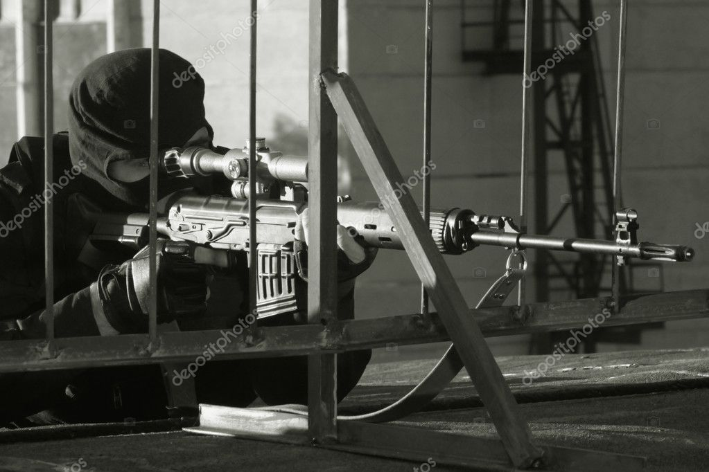 Sniper in a camouflage on a house roof shoots from a rifle.  — Stock Photo #3340652