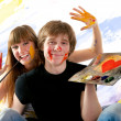 Young couple playing with painting — Stock Photo