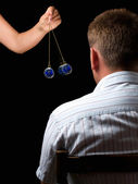 Woman hypnotizes man with a swinging watch during hypnotic treatment. — Stock Photo