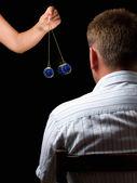 Vrouw hypnotiseert man met een swingende horloge tijdens hypnotische behandeling. — Stockfoto
