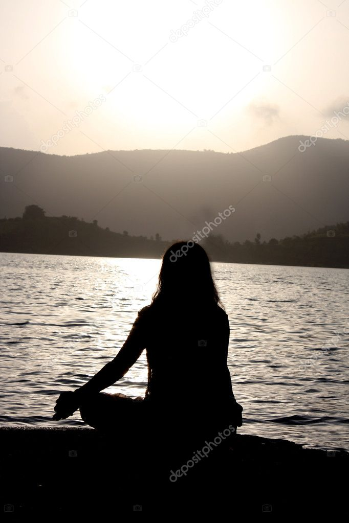 A spiritual Indian woman meditating on the riverbanks, in the morning. — Stock Photo #2986913