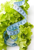 Meaasuring tape over fresh lettuce — Stock Photo