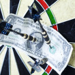 Darts target and dollar in bull's-eye — Stok fotoğraf