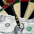 Darts target and dollar in bull's-eye — Stockfoto