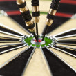Dart on bulls eye target of dartboard — Stock Photo