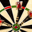 Dartboard with three darts in a bulls eye — Stock Photo