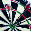 Dartboard with three darts in a bulls eye — Stock Photo #3792499