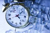 Classical Clock among ice cubes — Stock Photo