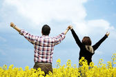 Young couple in a rape field — Stok fotoğraf