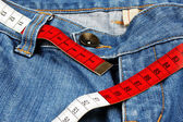 Blue jeans and measure tape isolated — Stock Photo