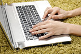 Woman with laptop on the carpet — Stock Photo