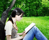 Young woman reading a novel — Stockfoto