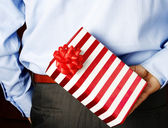 Businessman hiding a gift — Foto de Stock