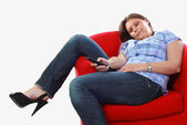 Girl on armchair with remote control — Stock Photo