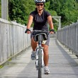 Cyclist crossing bridge — Stock Photo