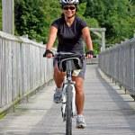 Cyclist crossing bridge — Stock Photo #3370892
