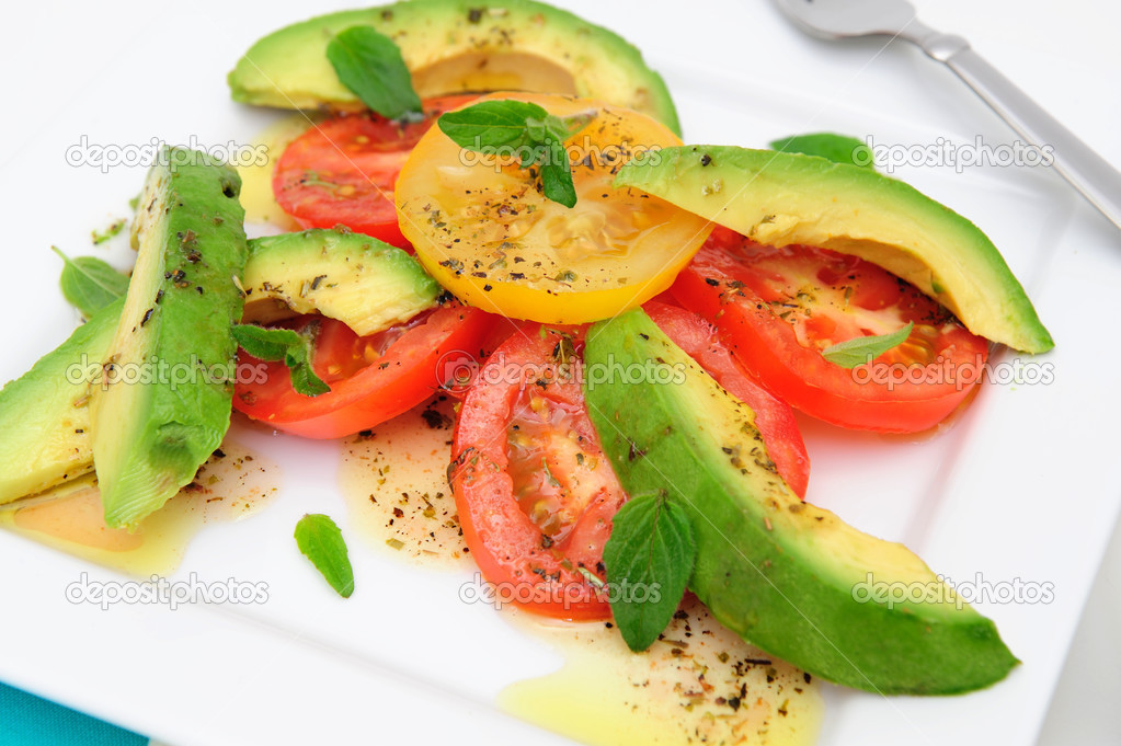 Red and yellow sliced tomatoes with  avocado, fresh oregano leaves with an olive oil and raspberry vinaigrette dressing on a square white plate.  Stock Photo #2904717