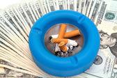 Dinheiro e cigarros cinzeiro — Foto Stock