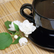 Black tea cup with jasmine — Stock Photo