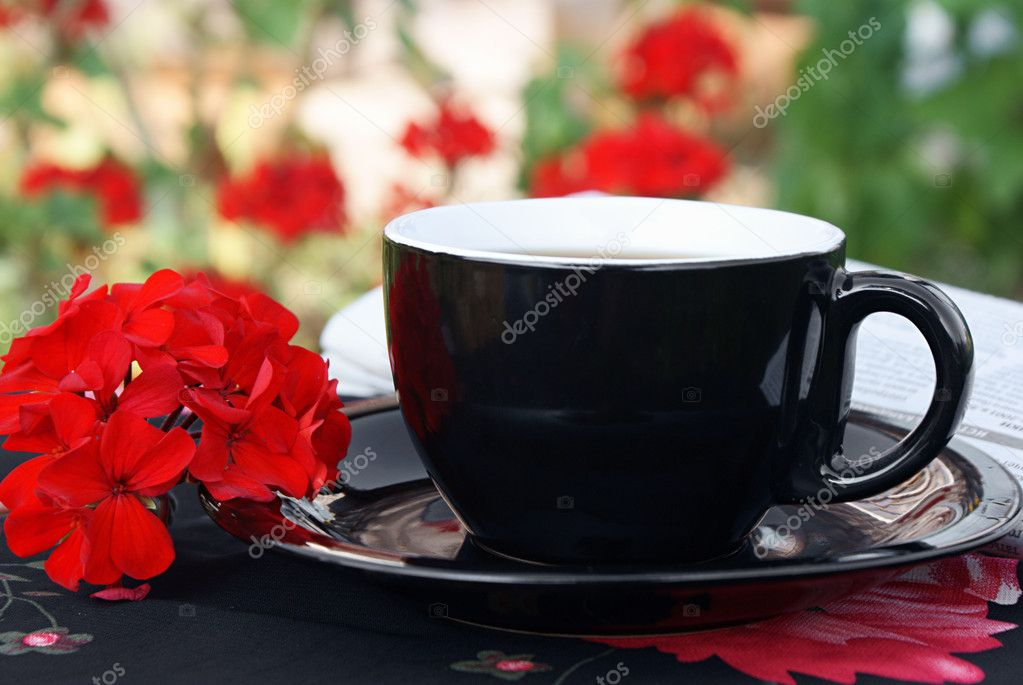Black cup of coffee with red flowers outdoor  Stock Photo #3741771