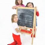 Little girls and blackboard — Stock Photo