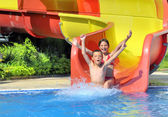Children sliding down a water slide — Stock Photo