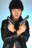 Asian man holding two guns in hands — Stock Photo
