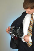 Young businessman looking at a clock — Stock Photo