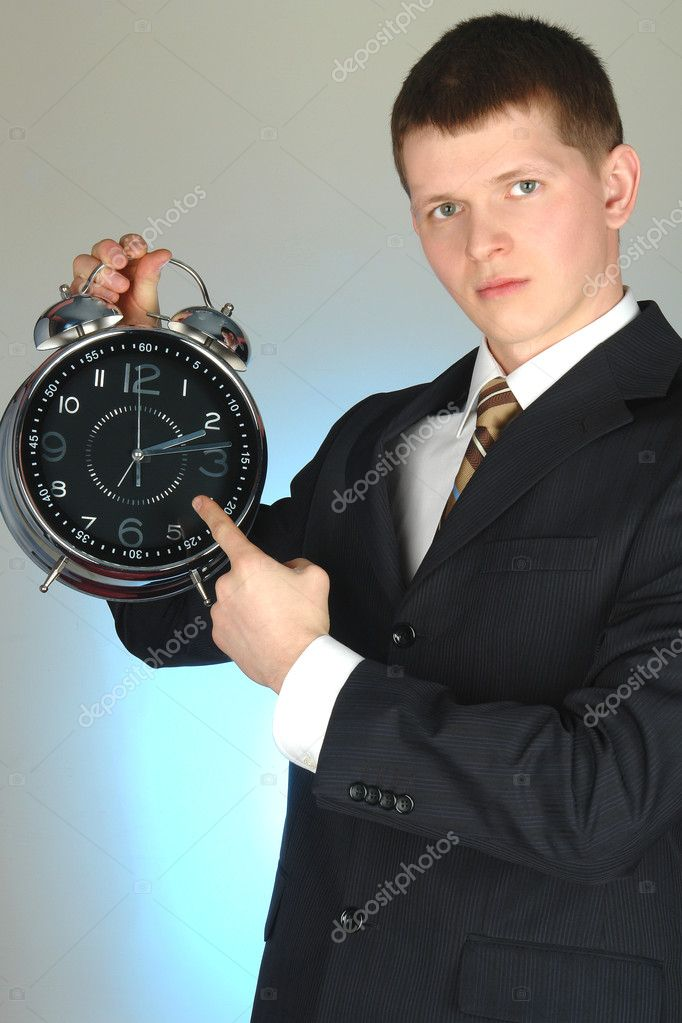 Young businessman holding big clock in hand                                 Stock Photo #2841394