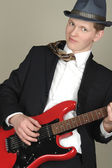Businessman with red guitar in hat — Stock Photo
