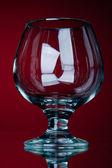 Ein leeres rebe glas auf einem roten — Stockfoto