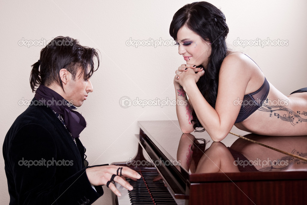 Fashionable Latino man playing the piano for a woman in bikini. — Stock Photo #2700233