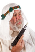 Arab Man Blowing on Money Stuffed in a Gun — Stock Photo