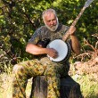 Older MPlaying Banjo Outdoors — Stock Photo #3455919