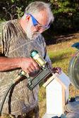 Homem sênior, construindo uma casa de pássaro — Foto Stock