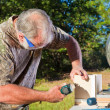 Man Uses a Nail Gun - Stock Photo